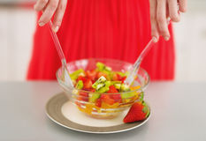 Closeup on young woman mixing fresh fruits salad Royalty Free Stock Image