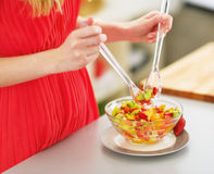 Closeup on young woman mixing fresh fruits salad Stock Photography