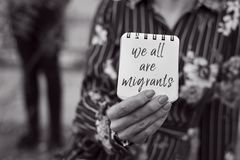 Woman and note with the text we all are migrants stock photo
