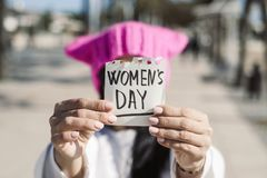 Woman with a pink hat and the text womens day stock photos