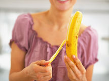 Closeup on young woman peeling banana Stock Images