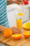 Closeup on young woman pouring fresh orange juice Royalty Free Stock Images