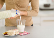 Closeup on young woman pouring milk into glass Stock Photo