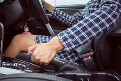 Closeup of young woman pulling handbrake lever Stock Photos