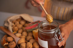 Closeup on young woman putting honey dipper in honey jar Royalty Free Stock Photos