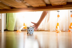 Closeup of young woman reaching under the bed and pressing snooz. Closeup photo of young woman reaching under the bed and pressing snooze button on alarm clock Stock Photos