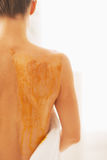 Closeup on young woman receiving honey spa therapy. rear view Royalty Free Stock Photography