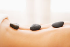 Closeup on young woman receiving hot stone massage Royalty Free Stock Photos