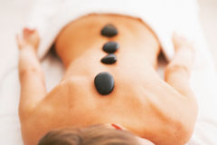 Closeup on young woman receiving hot stone massage Royalty Free Stock Photo
