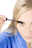 Closeup of young woman's face putting mascara. (pure white background Stock Photo