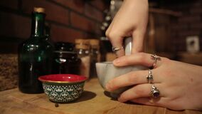 Closeup: Young woman`s hands grind spices using a Mortar and Pestle