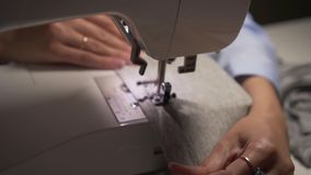 Woman`s hands sewing with a sewing machine. Women`s hands sew on a sewing machine. Fashion, creation and tailoring. Closeup of a young woman`s hands sewing with stock video