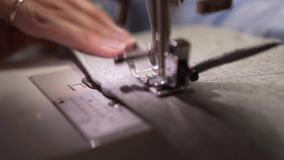 Woman`s hands sewing with a sewing machine. Women`s hands sew on a sewing machine. Fashion, creation and tailoring. Closeup of a young woman`s hands sewing with stock footage