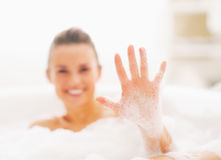 Closeup on young woman showing hand in foam Stock Photography