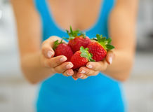 Closeup on young woman showing strawberries Royalty Free Stock Image