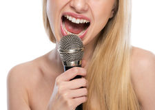 Closeup on young woman singing with microphone Stock Photography