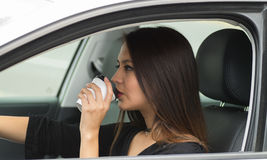 Closeup young woman sitting in car holding coffee cup and drinking, as seen from outside drivers window, female driver Stock Images