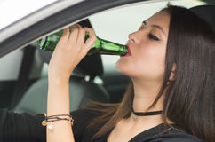 Closeup young woman sitting in car holding green beer bottle and drinking, as seen from outside drivers window, female Stock Images