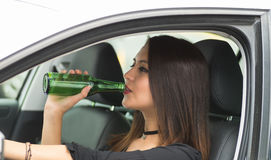 Closeup young woman sitting in car holding green beer bottle and drinking, as seen from outside drivers window, female Royalty Free Stock Photos