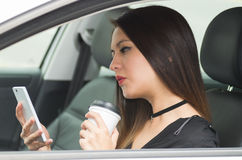 Closeup young woman sitting in car holding mobile phone and coffee cup, as seen from outside drivers window, female. Driver concept Royalty Free Stock Photos