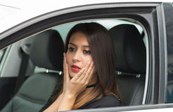 Closeup young woman sitting in car interacting slightly shocked, as seen from outside drivers window, female driver Royalty Free Stock Photos