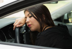 Closeup young woman sitting in car interacting tired and sleeping, as seen from outside drivers window, female driver Stock Photography
