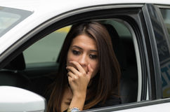Closeup young woman sitting in car interacting using body language, as seen from outside drivers window, female driver Stock Photos