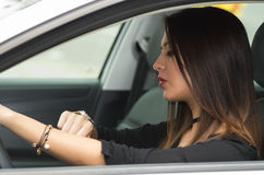 Closeup young woman sitting in car looking at wrist watch, as seen from outside drivers window, female driver concept Royalty Free Stock Photography