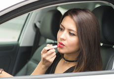 Closeup young woman sitting in car putting on makeup looking in mirror, as seen from outside drivers window, female. Driver concept Royalty Free Stock Photos