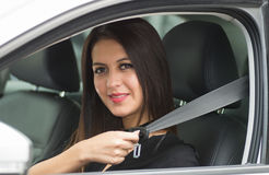 Closeup young woman sitting in car putting on seatbelt, as seen from outside drivers window, female driver concept Stock Photo