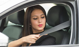 Closeup young woman sitting in car putting on seatbelt, as seen from outside drivers window, female driver concept Royalty Free Stock Photos