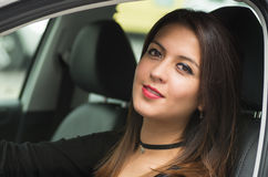 Closeup young woman sitting in car smiling to camera, as seen from outside drivers window, female driver concept Royalty Free Stock Images