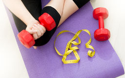 Closeup of young woman sitting on fitness mat and lifting dumbbe Royalty Free Stock Photography