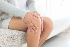 Closeup young woman sitting on sofa and feeling knee pain and sh. E massage her knee at home. Healthcare and medical concept stock images