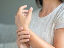 Closeup young woman sitting on sofa holds her wrist. hand injury. Feeling pain. Health care and medical concept stock photography