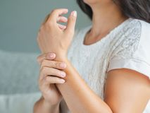 Closeup young woman sitting on sofa holds her wrist. hand injury stock images