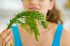 Closeup on young woman smelling fresh dill Royalty Free Stock Image