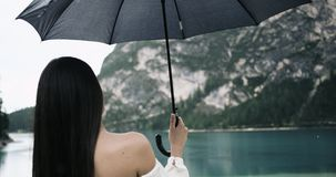 Closeup young woman stay with her back and naked shoulder to camera under her black umbrella and are looking to amazing. Sparkling lake stock footage
