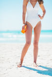 Closeup on young woman with sun block creme on beach Stock Photography