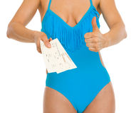 Closeup on woman in swimsuit showing air tickets Royalty Free Stock Photos