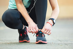 Closeup young woman tying her laces before a run. Royalty Free Stock Photos