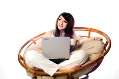 Closeup of a young woman using laptop. Young women is resting on the couch and surfing the internet on her laptop computer Stock Image