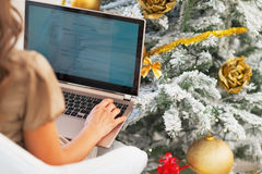 Closeup on young woman using laptop near christmas tree Royalty Free Stock Photo