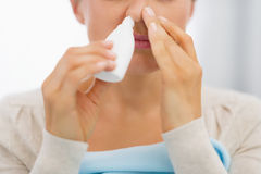 Closeup on young woman using nose drops Royalty Free Stock Image