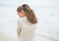 Closeup on young woman walking on cold beach Royalty Free Stock Images