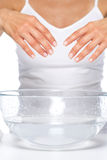 Closeup on young woman washing hands in glass bowl with water Royalty Free Stock Image