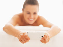 Closeup on young woman writing sms while laying on massage table Stock Photography