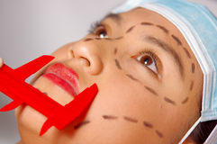 Closeup young womans face preparing for cosmetic surgery with lines drawn on skin, doctor measuring using red tool, as. Seen from above Stock Photo