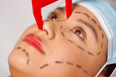 Closeup young womans face preparing for cosmetic surgery with lines drawn on skin, doctor measuring using red tool, as Royalty Free Stock Photos
