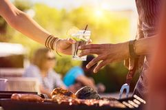 Woman sharing drink at bbq. Closeup of young women hand passing a drink to a men while preparing barbeque. Girl sharing glass with fresh lime juice during royalty free stock photo